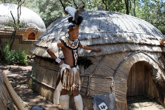 Zulu Mann mit traditioneller Kleidung vor einer Rundhütte in Zululand in Südafrika